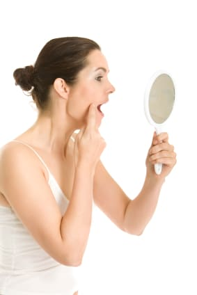 Woman inspecting her skin with hand mirror